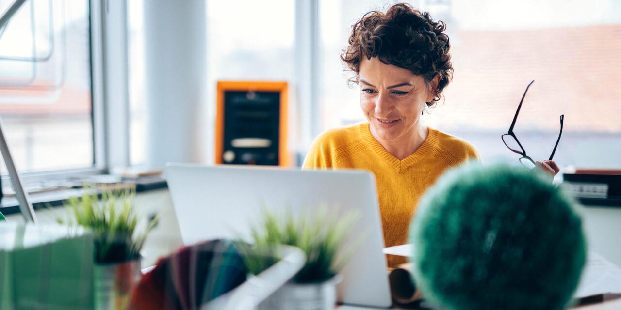 Frau mit Brille vor Computer am Arbeitsplatz