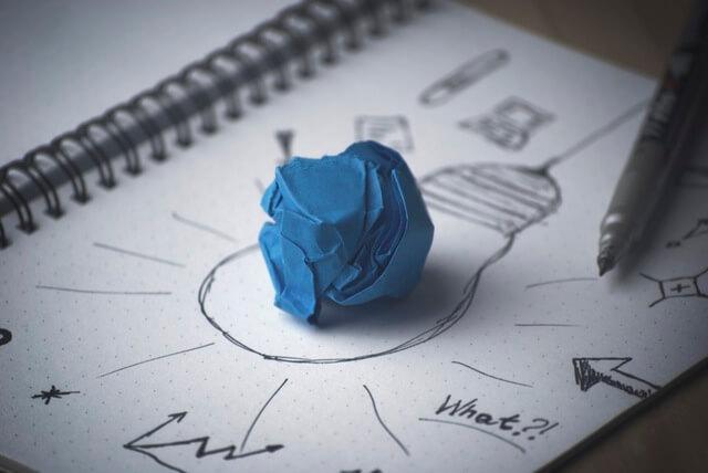 Ideenskizze mit Stift und blauem Papierknäuel