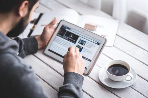 Mann mit Tablett-Rechner und Kaffee, der an einem Tisch sitzt.