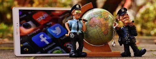 Stilleben mit Globus, Tablet und Polizeifiguren zu Online Recht