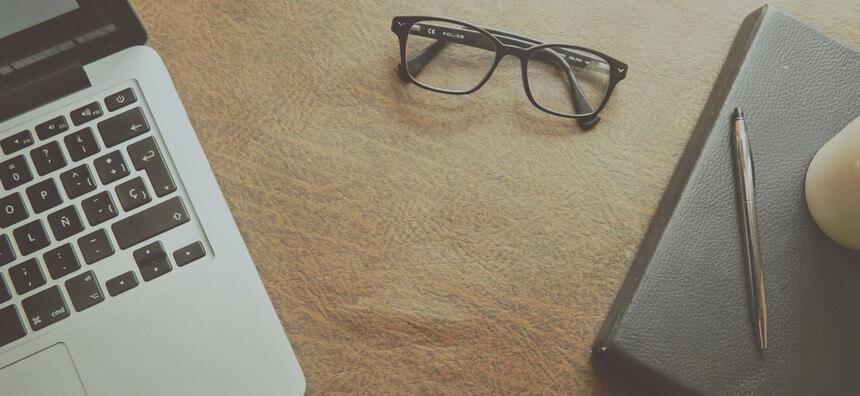Tisch mit Laptop, Brille, Notizblock und Stift - der typische Arbeitsplatz im Fernstudium
