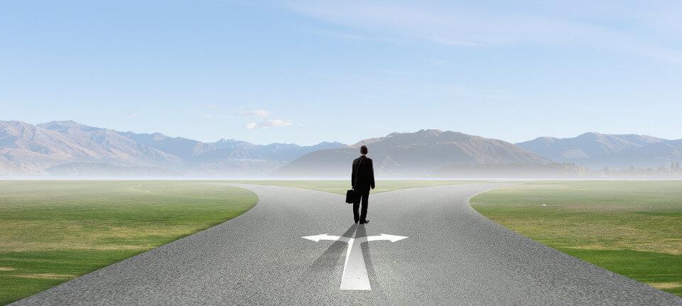 Person an Weggabelung vor der Wahl seiner beruflichen Zukunft