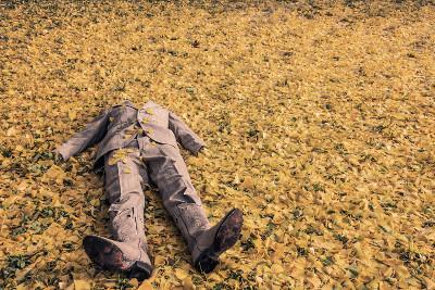 Kopflose Person in einem Haufen gelber Blätter