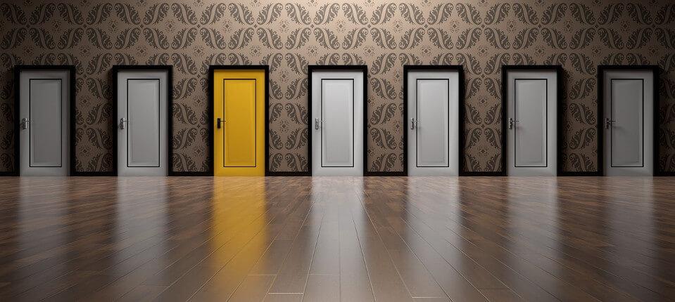 Sechs weiße Türen und eine gelbe Tür zeigen den Entscheidungsweg von Arbeitsuchenden