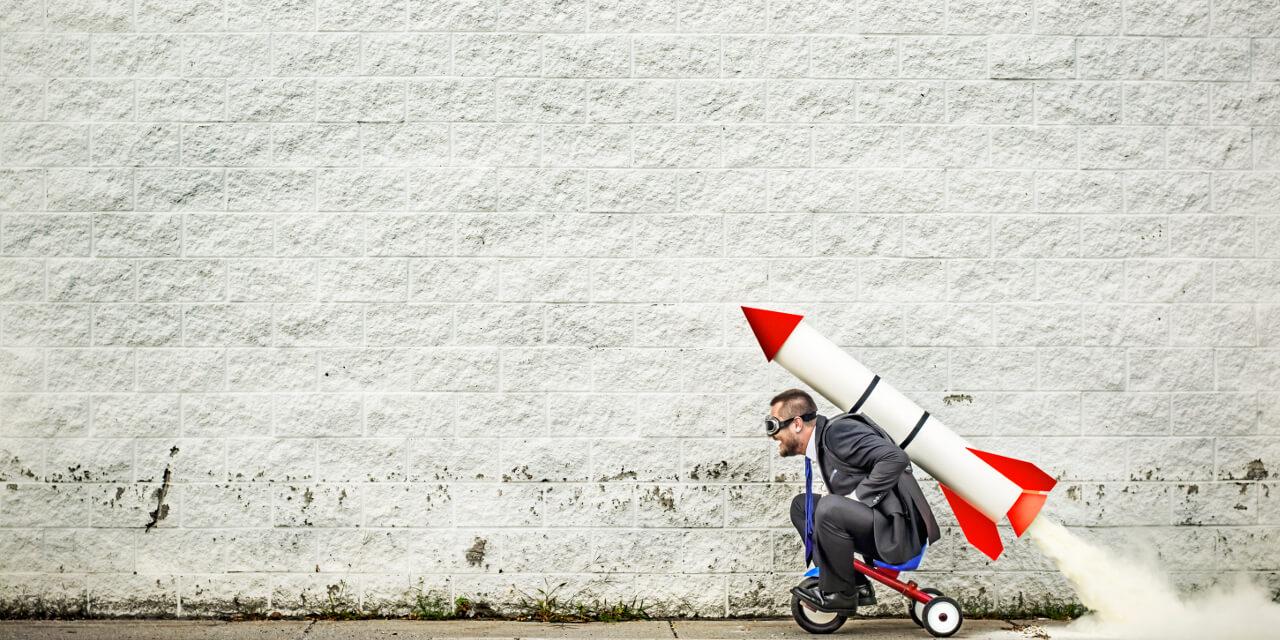 Business-Mann im Anzug auf Dreirad mit Rakete auf dem Rücken