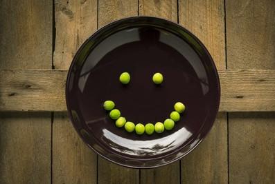 Smiley aus Erbsen auf einem Teiller