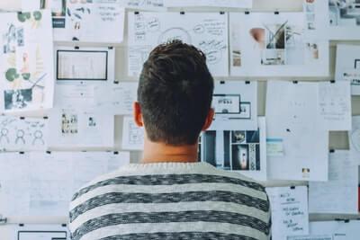 Projektmanager blickt bei der Arbeit auf eine Tafel