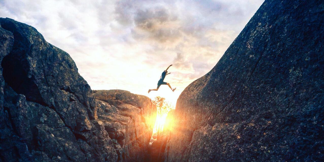 Sportler springt agil über eine Klippe