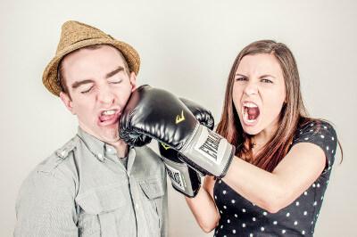 Humoristisches Bild einer jungen Frau mit Boxhandschuhen, die einen Mann boxt