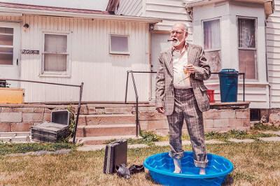 Älterer Herr mit Zigarre im Anzug steht in einem Pool