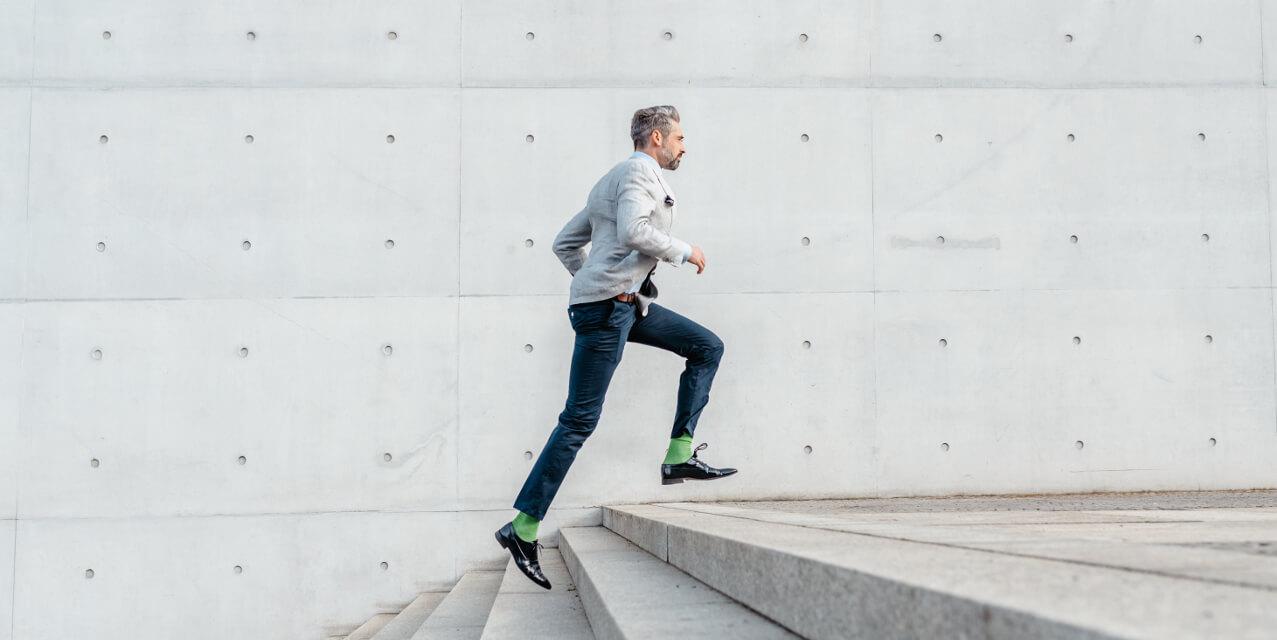 Business-Mann im hippen Anzug rennt die Treppe hoch