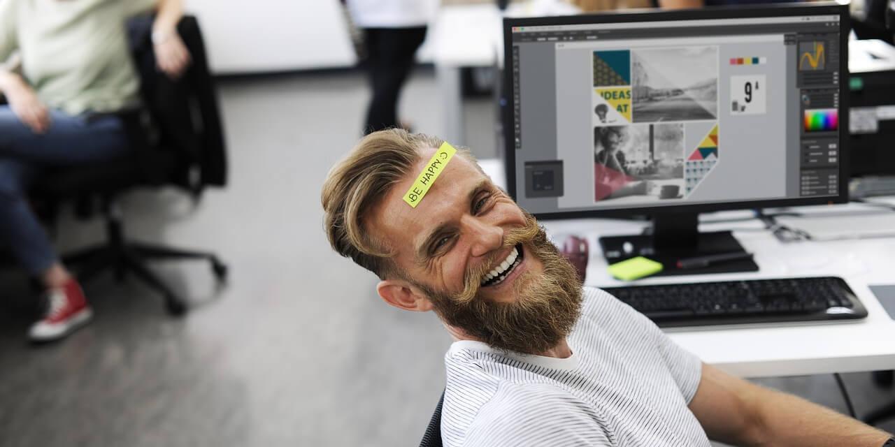Glücklicher Mitarbeiter (Hipster) am Arbeitsplatz