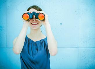 Junge Frau mit Fernglas sucht nach Talenten