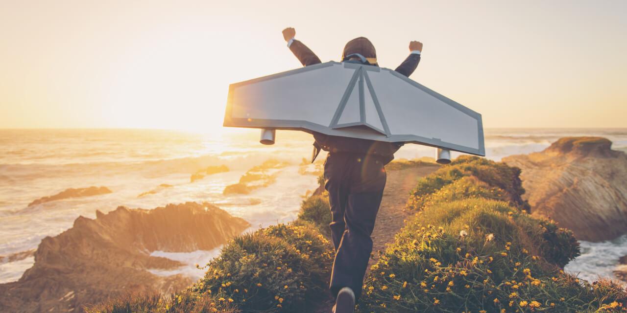 Junger Mensch im Anzug mit Flugzeugflügeln auf dem Rücken streckt die Arme in die Höhe