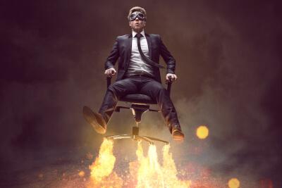 Mann im Anzug hebt mit Feuer unter'm Stuhl ab wie eine Rakete