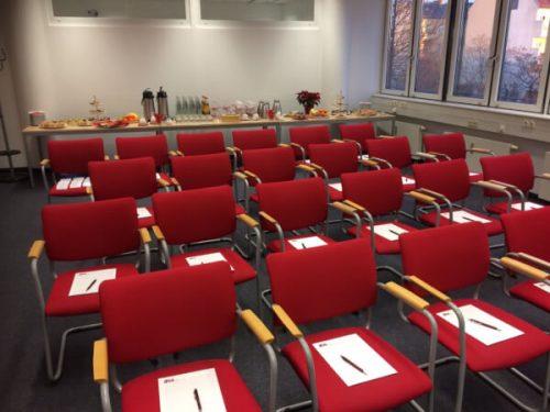 Wissensbrunch-Raum beim IFM mit Stühlen im roten Corporate Design und Unterlagen