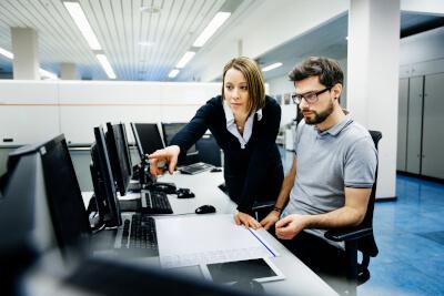 Zwei Mitarbeiter am PC zeigen, wie soziale Kompetenz in der IT-Administration zählt