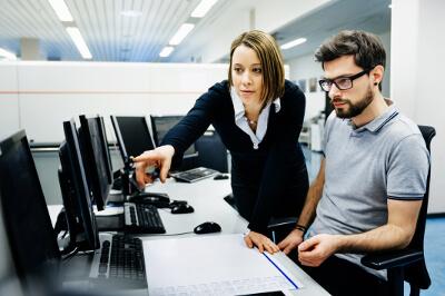 Mitarbeiterin und Mitarbeiter klären ein Problem am Arbeitsplatz umgeben von Computern