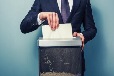 Unternehmer schiebt Dokument in den Aktenvernichter