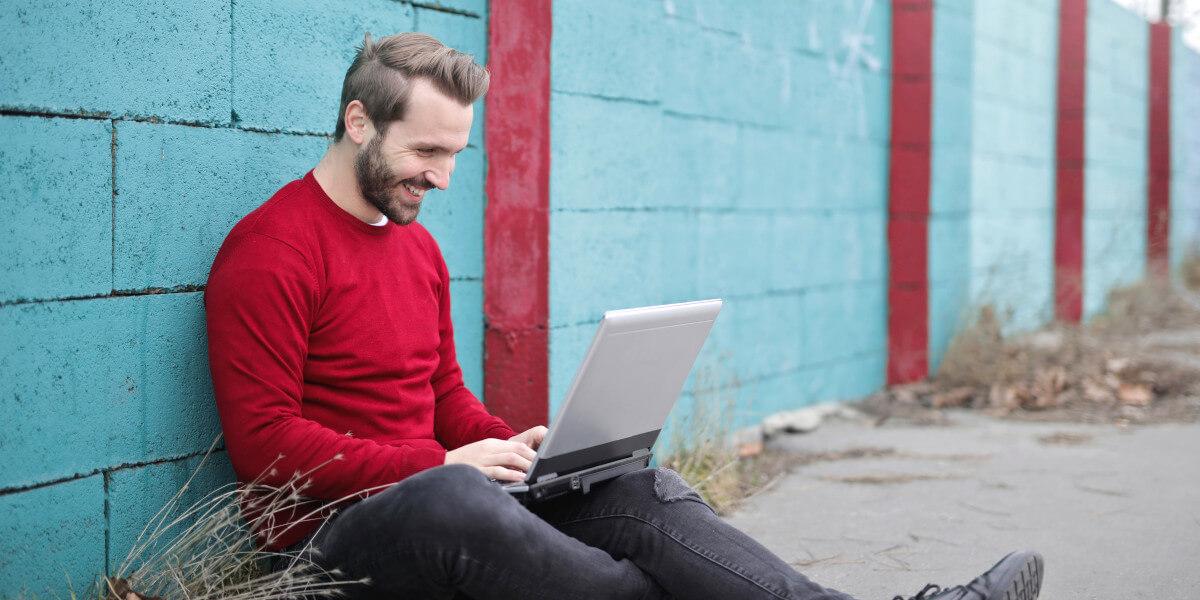 Junger Mann sitzt draußen mit Laptop und freut sich