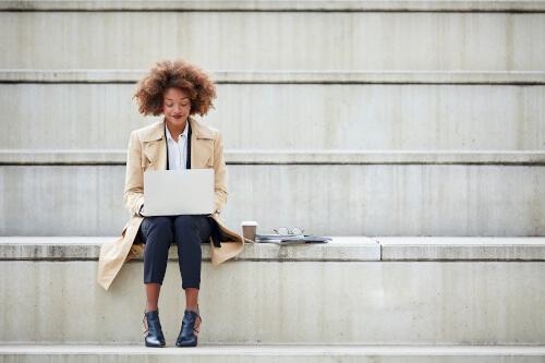 Junge Frau sitzt draußen auf einer Treppe mit Laptop
