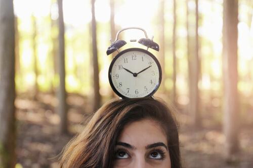 Junge Frau balanciert Wecker auf dem Kopf