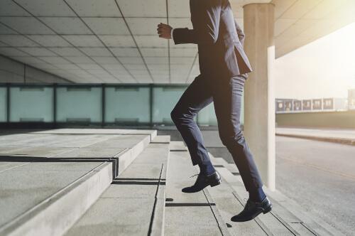 Mann im Anzug läuft die Treppe hoch