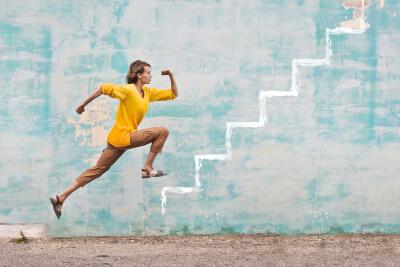 Junge Frau springt eine gezeichnete Treppe hoch