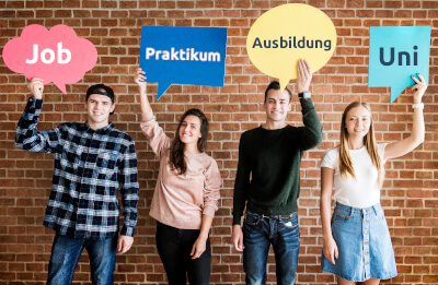 Jugendliche halten Schilder hoch mit Chancen für ihre Zukunft, wie Job oder Studium