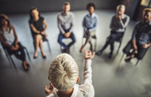 Trainerin steht vor eine Seminargruppe und vermittelt mit professioneller Gestik Expertenwissen