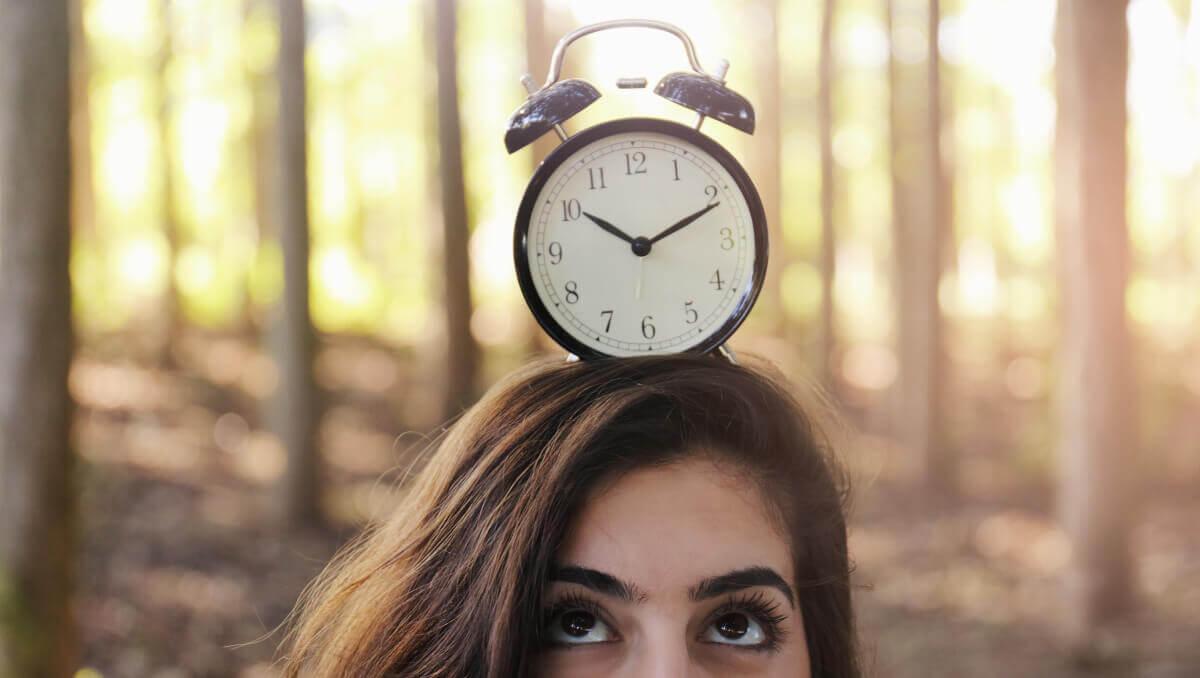 Frau mit Uhr auf dem Kopf blickt nach oben