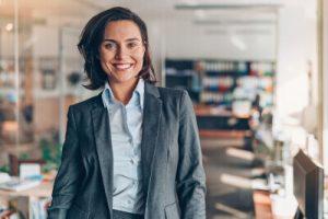 Frau im Anzug lacht mit Büro im Hintergrund