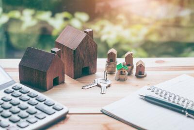 Tisch mit Haus, Schlüssel, Taschenrechner und Geld zeigt die Aufgaben eines Verwalters