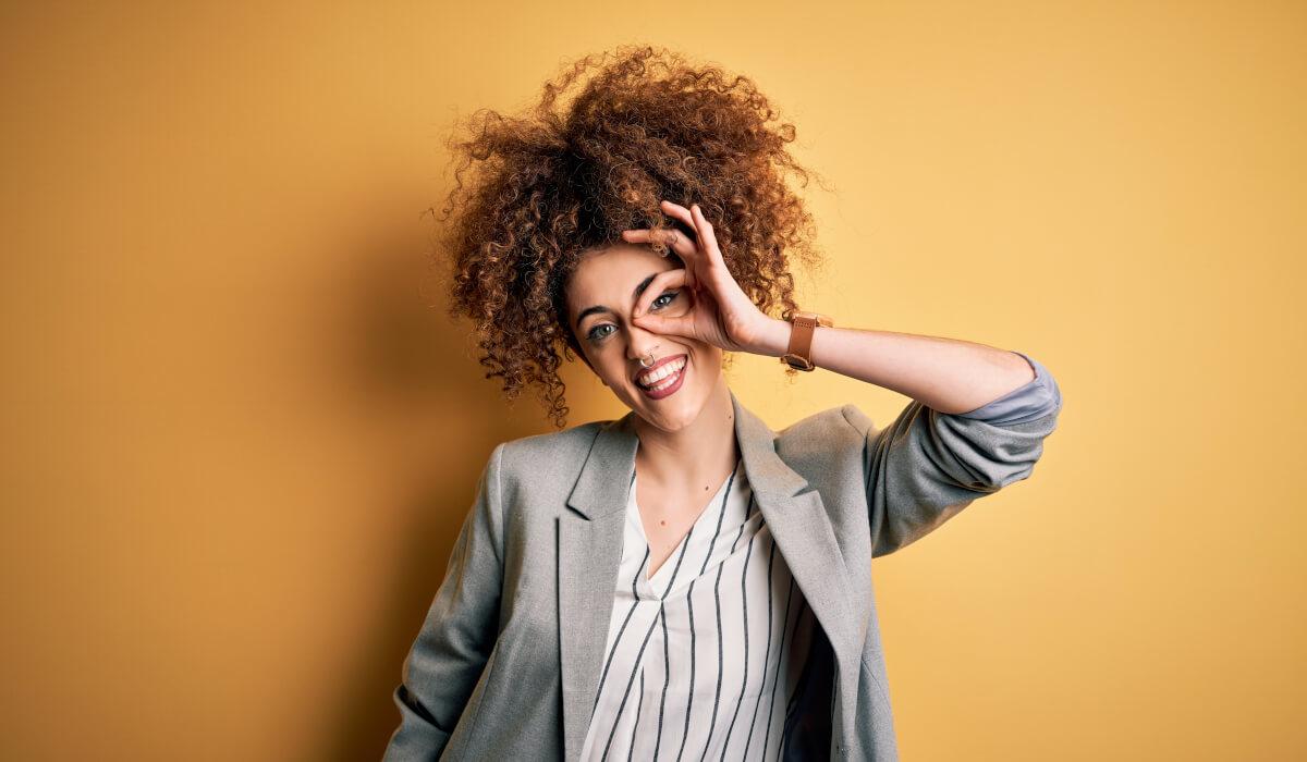 Junge Frau blickt mit einem Lachen in die Zukunft