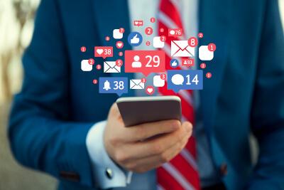 Business-Mann mit Smartphone in der Hand nutzt Social Media
