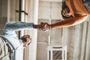 Mitarbeiter und Chefin schütteln sich die Hand auf Augenhöhe