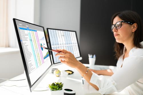Mitarbeiterin schaut auf eine Tabelle auf ihrem Monitor