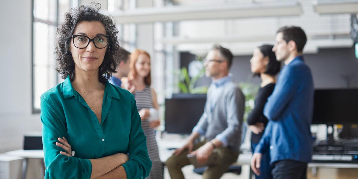 Professionelle Office Managerin mit ihrem Team im Hintergrund