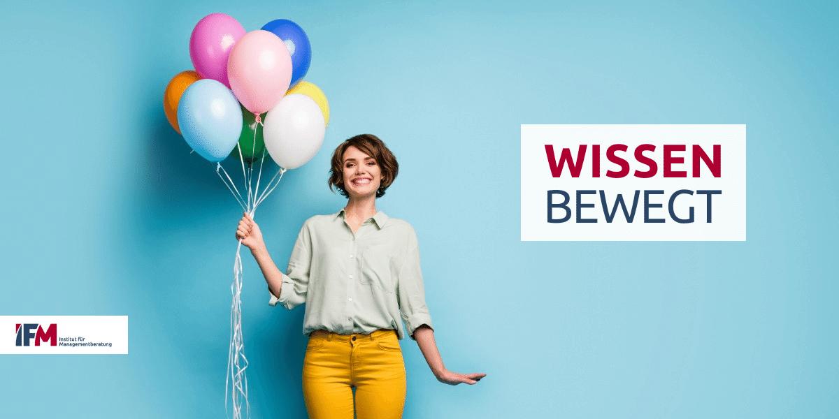 """Frau mit bunten Ballons zeigt das IFM-Logo und Motto """"Wissen Bewegt"""""""